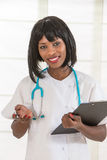 Black femeale nurse with clipboard using mobile phone,isolated against a white background. Stock Photos