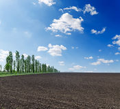 Black field under cloudy sky Royalty Free Stock Images