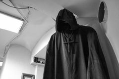Black figure in the shroud. The figure of death with a cross on his neck. A dark figure in the corner of the room in a robe and hood. The symbol of death. The Stock Photography