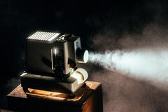 Black Film Projector Turned on Top of Wooden Table Royalty Free Stock Images