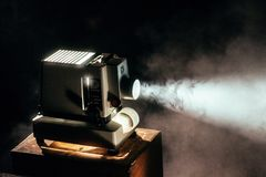 Black Film Projector Turned on Top of Wooden Table Stock Photo