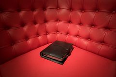 Black filofax on red leather couch Royalty Free Stock Photo
