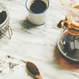 Black filtered coffee, square crop, copy space. Alternative brewing concept. Morning black filtered coffee and white cup and coffee ground in jar on light grey Stock Photography
