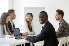 Black financial analyst using laptop analyzing statistics at mee. Smiling african businessman in suit looking at camera at multiracial team meeting, black royalty free stock image
