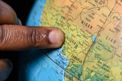 Black finger pointing Nigeria on a map. Finger of emigrant, pointing his homeland Nigeria on the world map royalty free stock photos