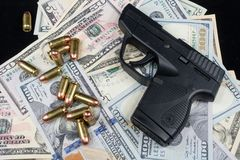 Black firearm and bullets  close-up on a pile of United States currency against a black background. Firearm and bullets on a pile of United States currency  and stock image
