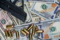 Black firearm and bullets  close-up on a pile of United States currency against a black background. Firearm and bullets on a pile of United States currency  and stock photo