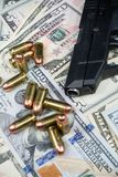 Black firearm and bullets  close-up on a pile of United States currency against a black background. Firearm and bullets on a pile of United States currency  and royalty free stock photography