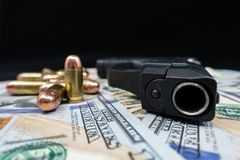 Black firearm and bullets  close-up on a pile of United States currency against a black background. Firearm and bullets on a pile of United States currency  and royalty free stock photo