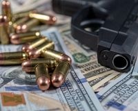 Black firearm and bullets  close-up on a pile of United States currency. Firearm and bullets on a pile of United States currency  and close-up. Finance,crime royalty free stock photo