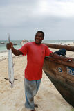 Black fisherman from the island of Zanzibar holding mackerel Stock Photo