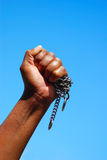 Black fist with chain. A black hand (fist) of an African American woman holding a rusty old chain in front of blue sky background Stock Photos