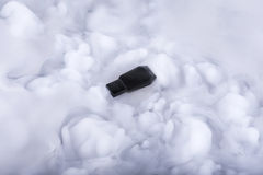 Black flash memory stick in the Information clouds Stock Image