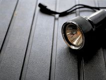 Black flashlight on rugged background. Black flashlight for camping on rugged background Stock Photography