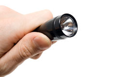 Black flashlight in a hand isolated. Stock Image