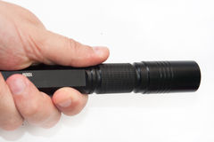 Black flashlight in hand on a white background Stock Image