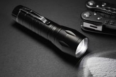 Black flashlight on the stone surface. Tools for work, search and tourism.  royalty free stock images