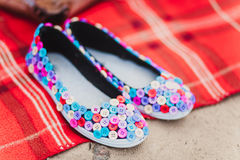 Black flat shoes made from textile covered with colored buttons. Handmade royalty free stock photo