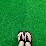 Black flip flops on green lush artificial grass, summer and vacations concept Stock Image