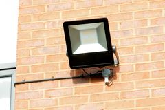 Office Exterior Floodlight. A black floodlight on the side of a red brick office Stock Photos