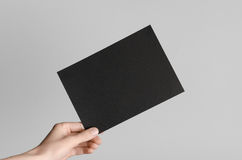 Black A5 Flyer / Invitation Mock-Up. Male hands holding black flyers on a gray background Stock Image