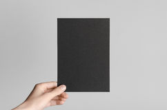 Black A5 Flyer / Invitation Mock-Up. Male hands holding black flyers on a gray background Stock Photography