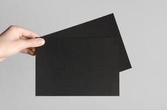 Black A5 Flyer / Invitation Mock-Up. Male hands holding black flyers on a gray background Stock Photo