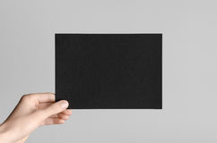 Black A5 Flyer / Invitation Mock-Up. Male hands holding black flyers on a gray background Stock Images