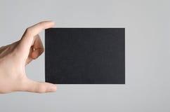 Black A6 Flyer / Postcard / Invitation Mock-Up. Male hands holding a black flyer on a gray background Stock Photos
