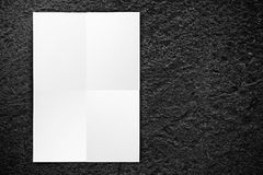 Black folded White paper poster hanging at black stone wall,Temp. Late mock up for adding your text royalty free stock photography