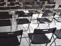 Black folding chairs stand in the white conference room stock photography
