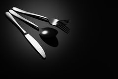 Black food background with knife, fork and spoon Royalty Free Stock Photography