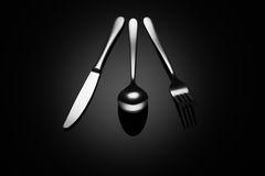Black food background with knife, fork and spoon Stock Photos
