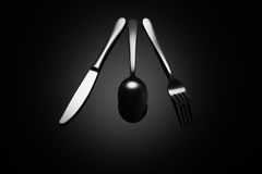 Black food background with knife, fork and spoon Royalty Free Stock Photo
