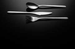 Black food background, silverware on reflective surface with copy space Stock Images