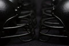 Black Football Helmets faceguard to faceguard Royalty Free Stock Image