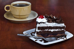 Black forest cake. On a table with cup of black coffee Royalty Free Stock Photos