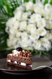 Black forest cake. Chocolate cake with cherry and bouquet of whi Royalty Free Stock Images