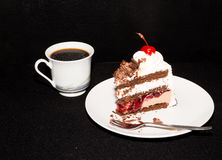 Black forest cake and coffee. Slice of Black Forest layer cake on white plate with fork and coffee Royalty Free Stock Images