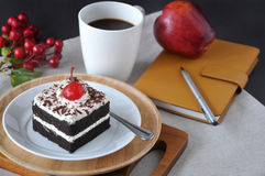 Black Forest Cake with Cup of Coffee. Dish of black forest cake and cup of coffee with notebook on table Stock Images