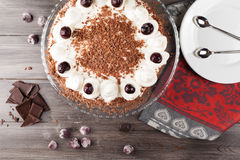 Black forest cake decorated with whipped cream and cherries. Stock Photos