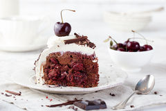 Black forest cake ,decorated with whipped cream and cherries Schwarzwald pie. Dark chocolate and cherry dessert on a white wooden background royalty free stock images