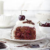 Black forest cake ,decorated with whipped cream and cherries Schwarzwald pie, dark chocolate and cherry dessert. On a white wooden background stock photo