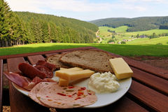 Black Forest hamand and cheese snack with bread with the beautiful view over a valley in the Black Forest, Germany Royalty Free Stock Photography