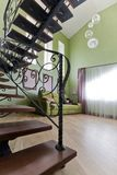 Black, forged staircase in a high, green interior stock photography