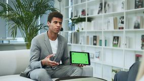 Black formal man making presentation with tablet with green chromakey screen. Young African-American man in suit sitting