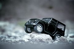 Black four wheel drive toy model car, explore in the forest