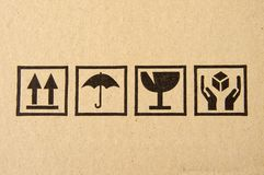 Black fragile symbol on cardboard. Image close-up of grunge black fragile symbol on cardboard stock photography
