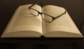 Black Frame Eyeglass in White Printed Book Page Royalty Free Stock Photos