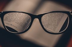 Black Frame Eyeglasses Behind Opened Book at Page 162 Royalty Free Stock Photo